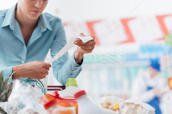 Woman checking a long receipt Stock photo © stokkete