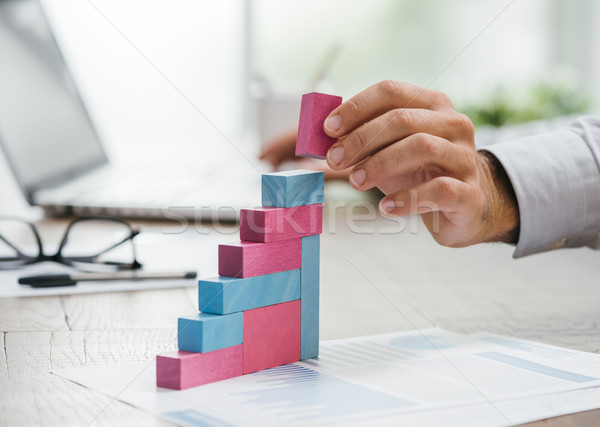 Businessman building a growing financial graph Stock photo © stokkete