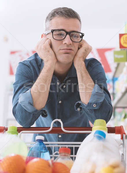 Sad man shopping at the supermarket Stock photo © stokkete