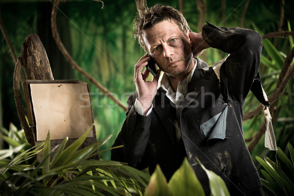 Businessman lost in jungle calling for help Stock photo © stokkete
