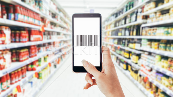 Woman scanning a barcode with her phone Stock photo © stokkete