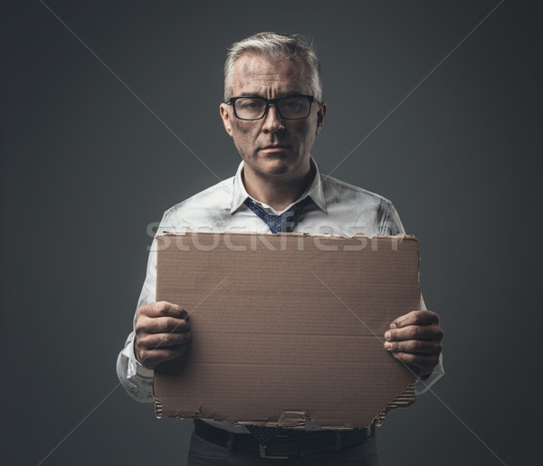 Broke jobless businessman holding a cardboard sign Stock photo © stokkete