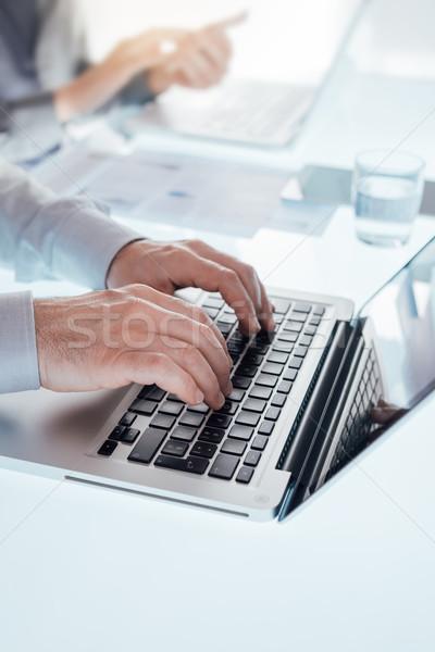 üzleti csapat dolgozik irodai asztal gépel laptop kezek Stock fotó © stokkete