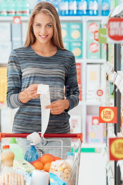 Happy woman with grocery receipt Stock photo © stokkete