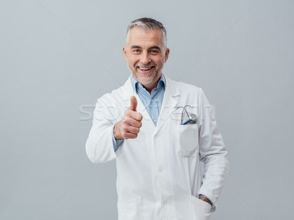 Cheerful doctor giving a thumbs up Stock photo © stokkete