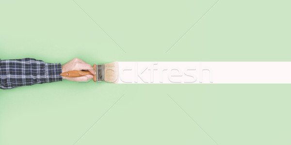 Man painting a wall with a paintbrush Stock photo © stokkete