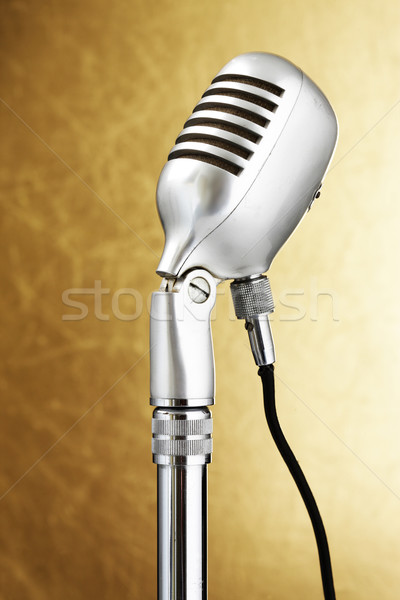 Retro style microphone. Gold background Stock photo © stokkete