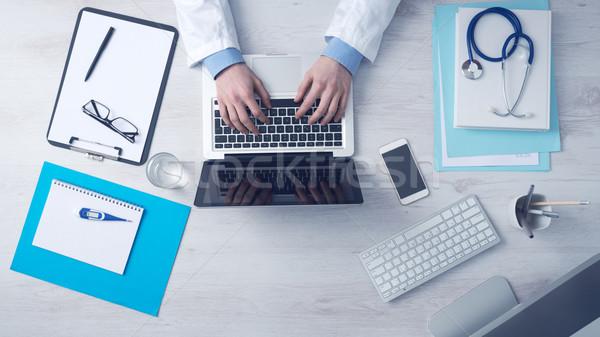 Orvos dolgozik irodai asztal ül laptop orvosi felszerelés Stock fotó © stokkete