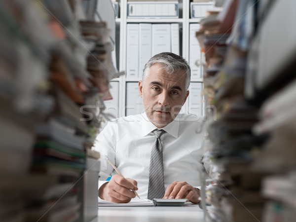 Frustrated businessman and piles of paperwork Stock photo © stokkete