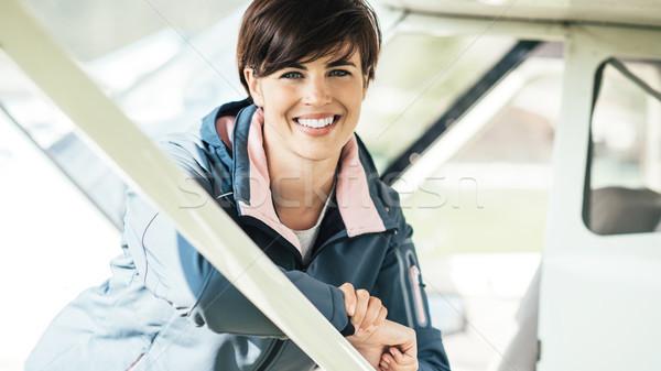 Fiatal mosolyog női pilóta dől repülőgép Stock fotó © stokkete