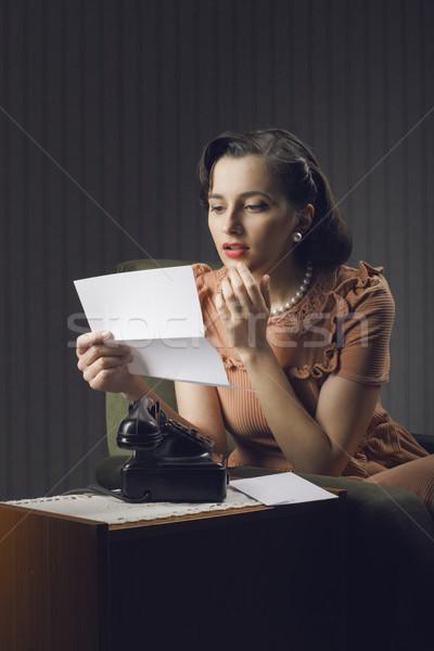 Fiatal nő olvas levél ül fotel nő Stock fotó © stokkete