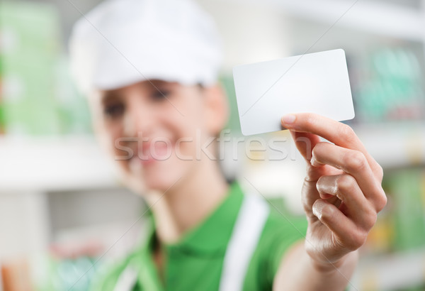 Sales clerk holding a blank business card Stock photo © stokkete