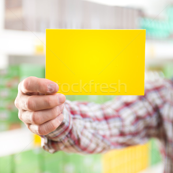 Man holding yellow sign at supermarket Stock photo © stokkete