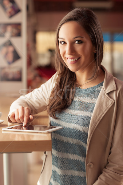 Smiling woman typing on her touch screen tablet Stock photo © stokkete