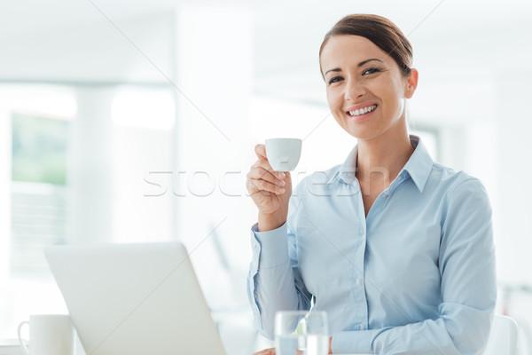 üzletasszony kávészünet mosolyog üzletasszony ül irodai asztal Stock fotó © stokkete