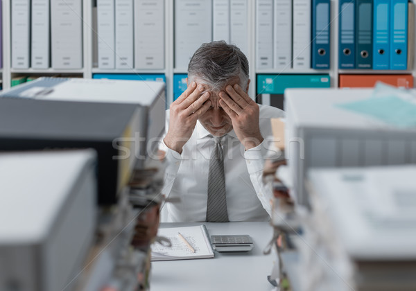 Stressed business executive and piles of paperwork Stock photo © stokkete