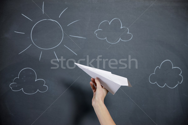 A female hand prepares to launch a paper airplane. Blackboard wi Stock photo © stokkete