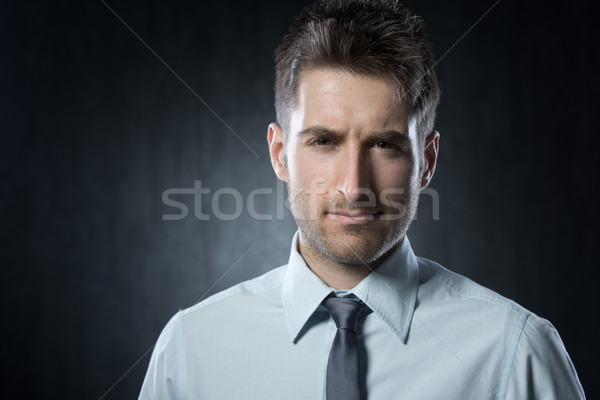 Gyanús üzletember fiatal néz kamera kétséges Stock fotó © stokkete