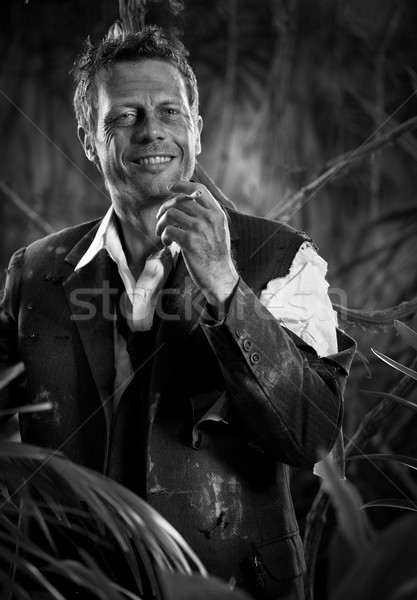 Businessman smoking in the jungle and waiting to be rescued Stock photo © stokkete