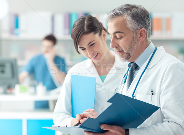 Doctor checking medical records with his assistant Stock photo © stokkete