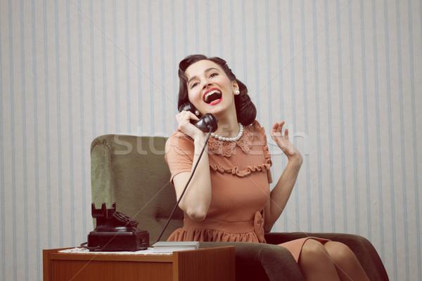 Cheerful woman talking on landline phone Stock photo © stokkete