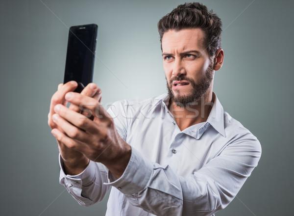 Hideg férfi elvesz jóképű férfi portrék okostelefon Stock fotó © stokkete