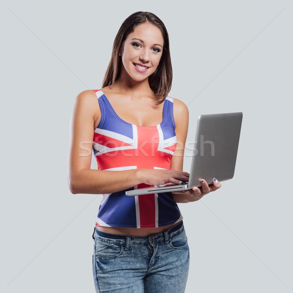 Glimlachend brits meisje laptop Stockfoto © stokkete