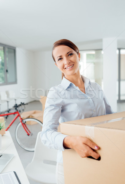 Happy woman carrying boxes into her new office Stock photo © stokkete