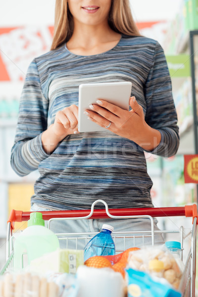 Woman using shopping apps on the tablet Stock photo © stokkete