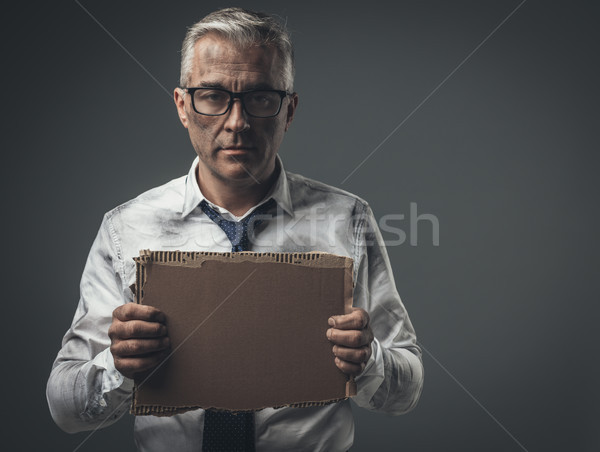 Broke jobless businessman holding a cardboard sign Stock photo © stokkete
