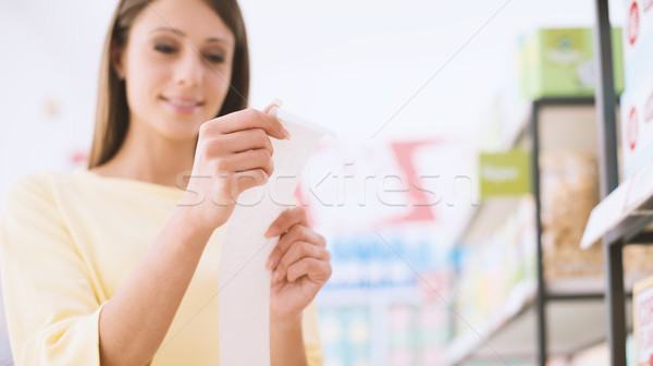 Woman checking the grocery receipt Stock photo © stokkete