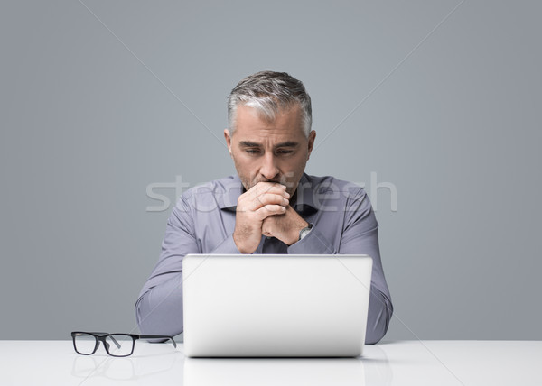 Pensive businessman working with a laptop Stock photo © stokkete