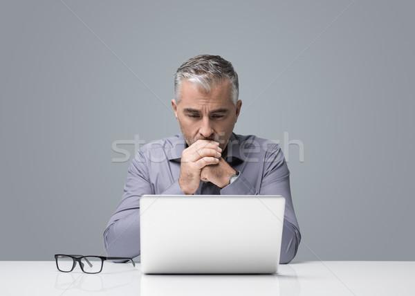 Töprengő üzletember dolgozik laptop érett ül Stock fotó © stokkete