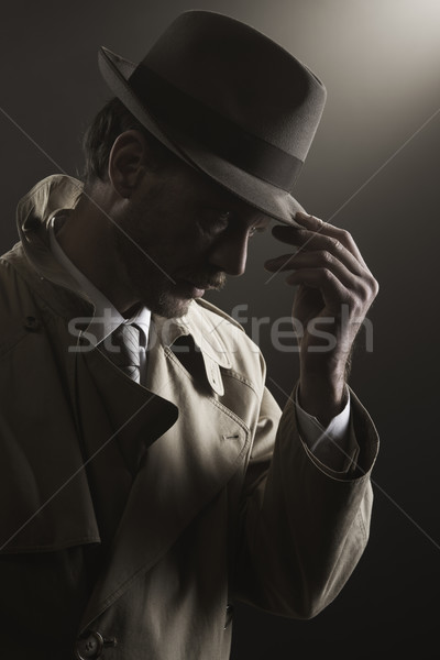 Detective adjusting his hat Stock photo © stokkete