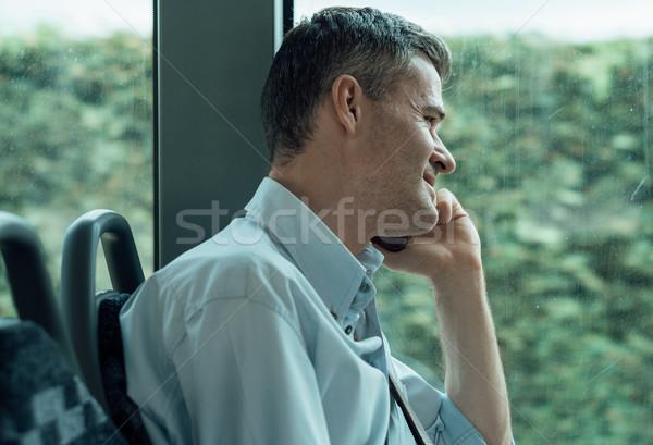 üzletember telefonbeszélgetés ingázás munka busz okostelefon Stock fotó © stokkete