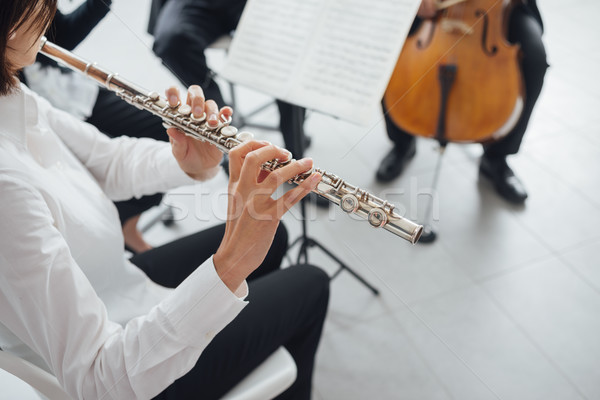 Stock photo: Flutist playing her instrument on stage