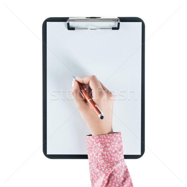 Stock photo: Woman writing on a clipboard