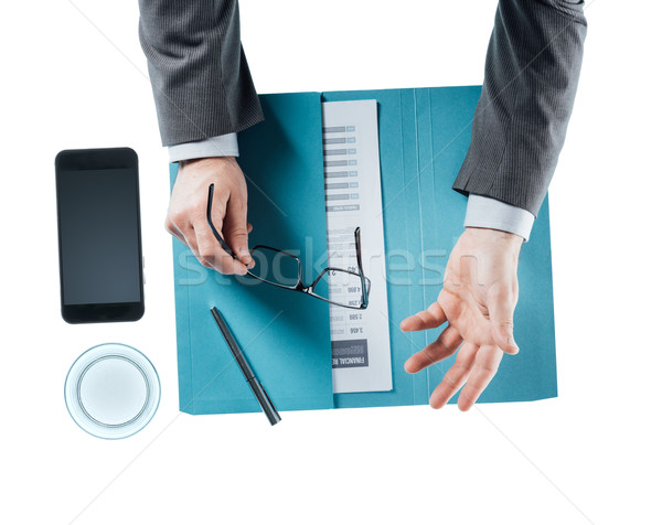 üzletember tart szemüveg beszél asztal gesztikulál Stock fotó © stokkete