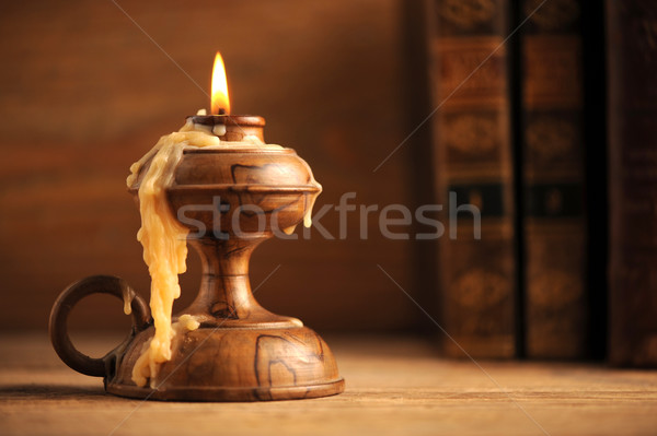 Stock photo: old candle on a wooden table, old books in the background