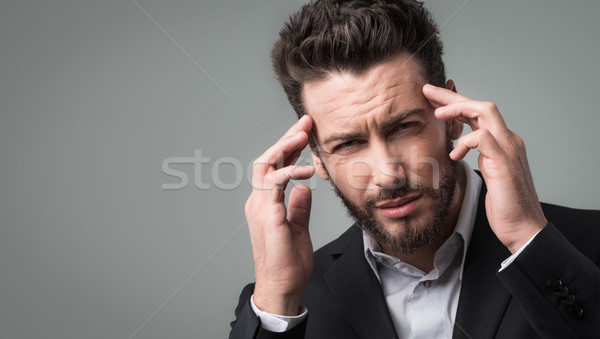 Businessman with headache head in hands Stock photo © stokkete
