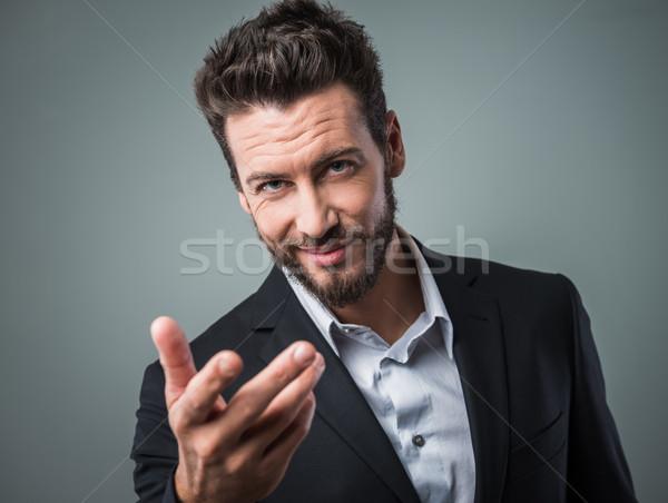 Vonzó férfi flörtöl nyitva kéz üzletember Stock fotó © stokkete
