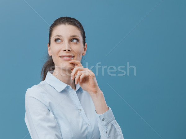 Confident woman thinking with hand on chin Stock photo © stokkete