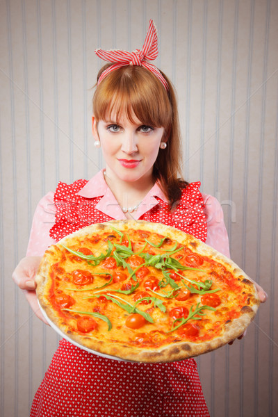 Retro Housewife holding a vegetarian pizza Stock photo © stokkete
