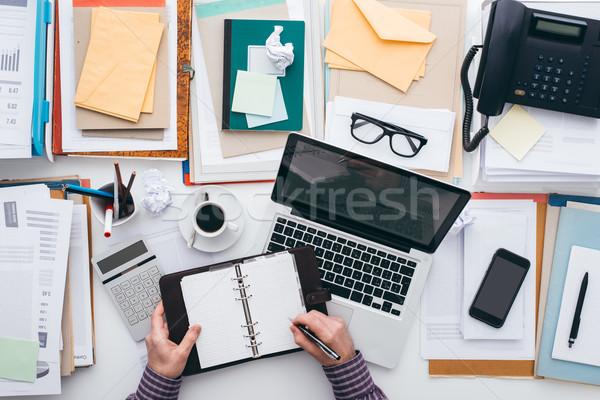 üzletember szervező tele asztali papírmunka laptop Stock fotó © stokkete