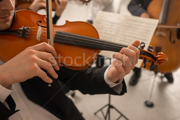 Stock photo: Violinist performing with orchestra