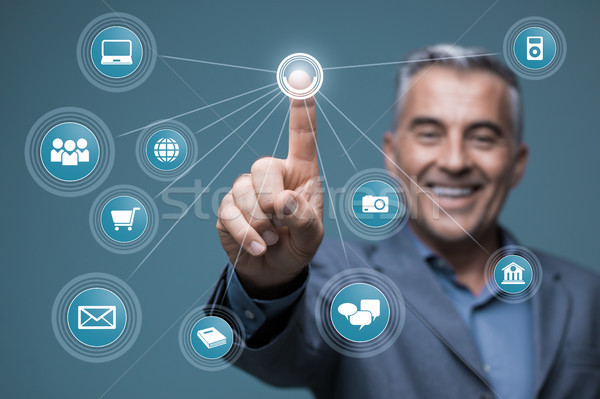 Smiling businessman using a virtual interface Stock photo © stokkete
