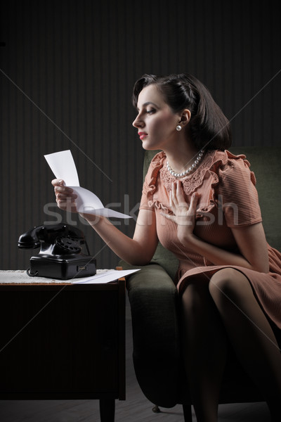 Young woman reading a letter sitting on armchair Stock photo © stokkete
