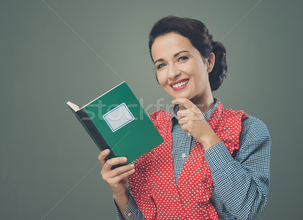 Femme souriante tablier livre de cuisine souriant rétro femme Photo stock © stokkete
