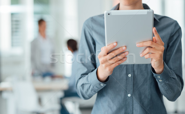 Confident business woman using a touch screen tablet Stock photo © stokkete