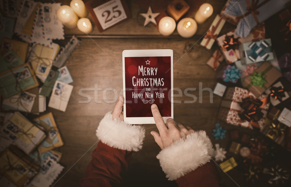 Stock photo: Santa Claus using a tablet